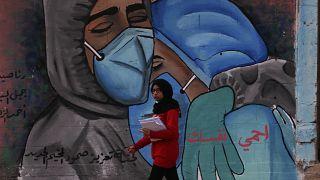 طالبة تمشي أمام لوحة جدارية تشجع على ارتداء كمامة للوقاية من فيروس كورونا، على الطريق الرئيسي لمخيم النصيرات، وسط قطاع غزة.