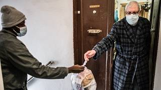 Lannseny delivers food to Piero, 74, in Livorno, Italy.