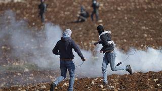 متظاهرون فلسطينيون يستخدمون المقلاع لرشق الحجارة باتجاه القوات الإسرائيلية خلال احتجاج ضد المستوطنات الإسرائيلية