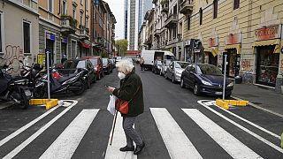 İtalya'da Covid-19 kısıtlamaları altında maske takarak dışarı çıkan yaşlı bir kadın.