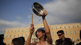 Yunanistan parlamentosu önünde tencere ve tavalara vurarak ses çıkarıp eylem yapan bir grup vatandaş.