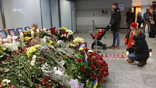 Flowers and candles are placed in front of portraits of the flight crew members of a Ukrainian jet that crashed near Tehran, at the Borispil airport, Ukraine, Jan. 11, 2020.