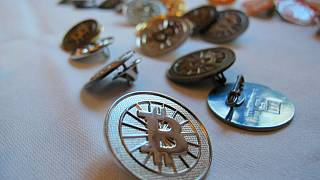 Bitcoin buttons are displayed on a table at the Inside Bitcoins conference in Berlin.