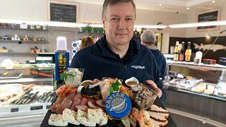 يقدم فالتر غرول  ، مزارع الأسماك وصاحب متجر لبيع الأطعمة الشهية، منتجاته بما في ذلك الكافيار الأبيض في بلدة غروديغ بالقرب من سالزبورغ، النمسا، 15 ديسمبر 2020