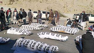 أفراد الطائفة الشيعية الهزارة يقفون حول الجثث بعد أن قتل مسلحون 11 عاملاً في منجم في منطقة ماخ الجبلية