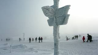 Personas juegas con la nieve junto a una señal helada en Schierke, Alemania