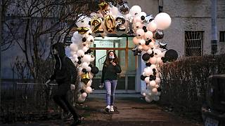 Children stand in the doorway of an apartment building, framed by a a new year's balloon decoration in Bucharest, Romania, Friday, Jan. 1, 2021.