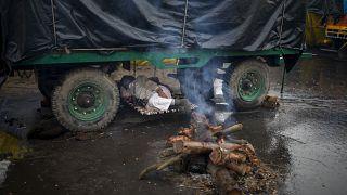 Un contadino si riposa sotto al suo trattore al confine tra gli Stati di Delhi e Uttar Pradesh, in India, lunedì 4 gennaio 2021