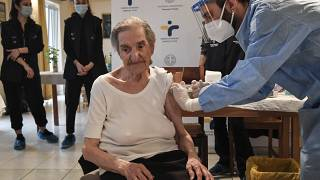An elderly woman gets a vaccination at a nursing house in Athens, Monday, Jan. 4, 2021