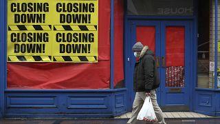 Una persona pasa ante una tienda cerrada en Escocia