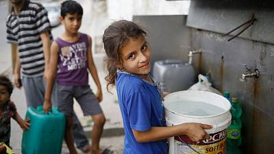 Thirteen-year-old Israa holds a bucket filled with potable water from a public water point in Khan Younis, Gaza Strip.