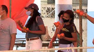 Un grupo de persnoas hacen cola para comprar pan con tomates en las manos