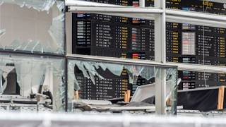 In this March 23, 2016 file photo, an arrivals and departure board is seen behind blown out windows at Zaventem Airport in Brussels.