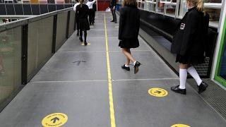 Pupils follow social distancing signs as they walk along a school corridor
