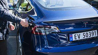 Archives : un propriétaire d'une Tesla Model S en train de recharger sa voiture le 3 mai 2019 à Oslo