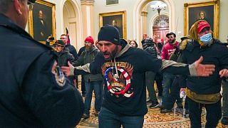 Partidarios de Trump se encaran contra la policía del Capitolio de EE.UU. en el pasillo fuera de la cámara del Senado en el Capitolio de Washington, el miércoles 6 de enero.