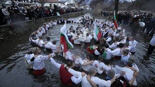 Dozens of citizens of the mountain town of Kalofer, in central Bulgaria, clad in traditional dresses stand in the icy Tundzha River