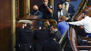 U.S. Capitol Police with guns drawn stand near a barricaded door as protesters try to break into the House Chamber at the U.S. Capitol on Wednesday, Jan. 6, 2021.