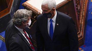 El vicepresidente Mike Pence habla con el representante republicano por Michigan Bill Huizenga durante una sesión conjunta del Congreso
