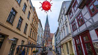 Coronavirus-Lampion hängt über einer Einkaufsstraße vor dem Turm des Schweriner Doms, 5.1.2021