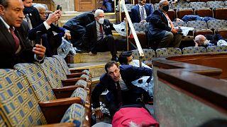La gente se refugia en la galería de la Cámara de Representantes mientras los manifestantes tratan de entrar en la Cámara de Representantes en el Capitolio de EE.UU.