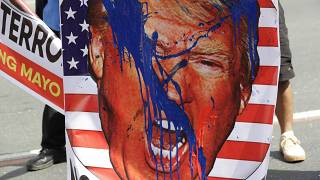An image of U.S. President Donald Trump is splashed with paint by protesters as they hold a rally opposing the recent attack of the U.S. against Iran, where it killed Soleiman