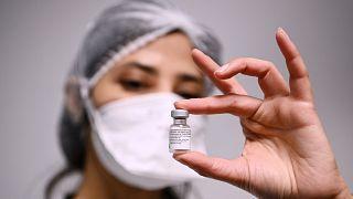 Сотрудница больницы в столичном регионе Франции с ампулой вакцины Pfizer/BioNTech