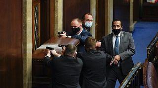 Policías del Capitolio defienden con sus armas en la mano una de las entradas de la Cámara de Representantes
