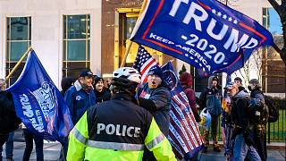 Pro-Trump supporters stand behind police as they argue with counter protesters during a confrontation near Black Lives Matter plaza in Washington, DC