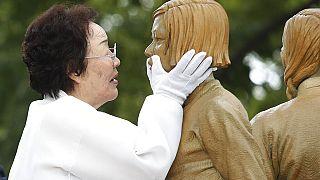 """II. Dünya Savaşı sırasında """"konfor kadın"""" olarak kullanılan bir mağdur anma töreninde anıta dokunurken"""