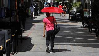 A woman shields herself from the sun with an umbrella amid a heatwave in Nicosia, Cyprus, Friday, Sept. 4, 2020.