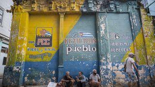Tres hombres con las mascarillas mal colocadas charlan sentandos delante de un muro con consignas políticas en La Habana