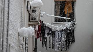 Frozen laundry hangs on a line outside an apartment window after a heavy snowfall in Madrid, Spain, Saturday, Jan. 9, 2021.