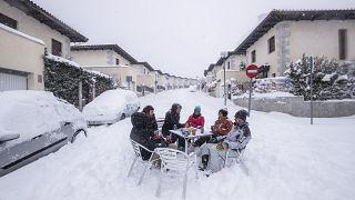 Unos vecinos beben en medio de la calle durante una fuerte nevada en Bustarviejo, en las afueras de Madrid, España, el  9 de enero de 2021.