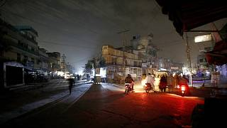 People are silhouetted on vehicles headlights on a dark street during widespread power outages in Rawalpindi, Pakistan, Sunday, Jan. 10, 2021.