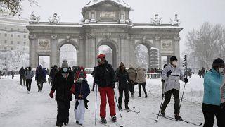 """La gente delante de """"La Puerta de Alcalá"""" durante la fuerte nevada en el centro de Madrid, España, el 9 de enero de 2021."""