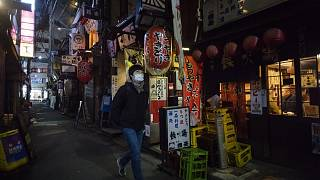 A man walks through an alley filled with restaurants and bars after 8 p.m. on the first day of a coronavirus state of emergency in Tokyo on Friday, Jan. 8, 2021.