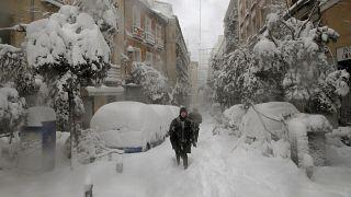 People walk during a heavy snowfall in Madrid, Spain, Saturday, Jan. 9, 2021