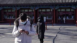 A man wearing a face mask to help curb the spread of the coronavirus browses his smartphone as a masked security guard stands near the quiet ticket counters in Beijing.