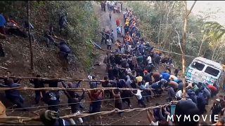 روستاییان هندی با شاخههای انگور کامیونی را از یک دره بیرون آوردند