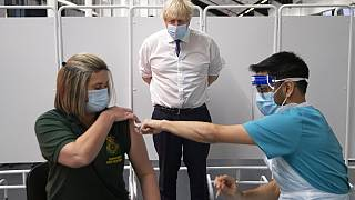 Britain's Prime Minister Boris Johnson watches first responder Caroline Cook receiving an injection of a Covid-19 vaccine at Ashton Gate Stadium in Bristol, England