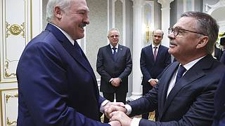 Belarusian President Alexander Lukashenko, left, greets International Ice Hockey Federation President Rene Fasel during their meeting in Minsk, Belarus, Monday, Jan. 11, 2021.