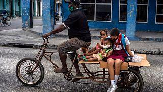Un hombre lleva a tres niños en su triciclo en La Habana, Cuba