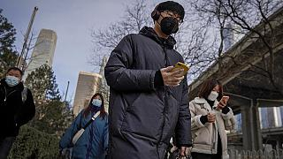A man wearing a face mask and a disposable gloves to help curb the spread of the coronavirus heads to work with other masked people during the morning rush hour in Beijing.