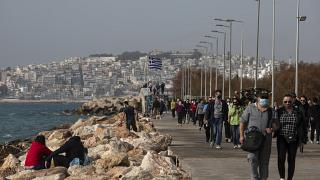 People walk on a promenade at Alimos suburb, south of Athens, Sunday, Jan. 10, 2021.