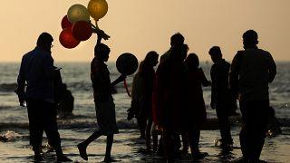 صبي يبيع بالونات على شاطئ جوهو في مومباي في الهند. 2020/12/26