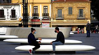 Men wearing face masks to prevent the spread of coronavirus talk on a bench at Elefphtheria, Liberty, square in central Nicosia