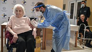 An elderly woman gets a vaccination at a nursing house in Athens