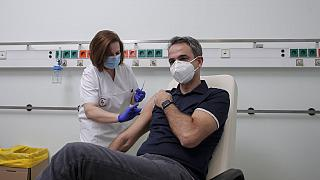 Greece's Prime Minister Kyriakos Mitsotakis receives an injection with a dose of COVID-19 vaccine
