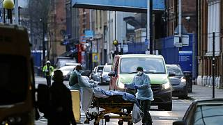 A patient is pushed on a trolley outside the Royal London Hospital in east London, Tuesday, Jan. 12, 2021.